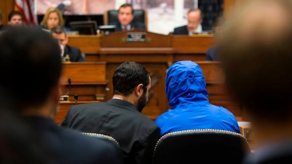 ATTENTION EDITORS - VISUAL COVERAGE OF SCENES OF INJURY OR DEATH The man credited with smuggling 50,000 photos said to document Syrian government atrocities, a Syrian Army defector known by the protective alias Caesar (disguised in a hooded blue jacket), listens to his interpreter as he prepares to speak at a briefing to the House Foreign Affairs Committee on Capitol Hill in Washington July 31, 2014. REUTERS/Jonathan Ernst (UNITED STATES - Tags: POLITICS MILITARY CONFLICT) TEMPLATE OUT