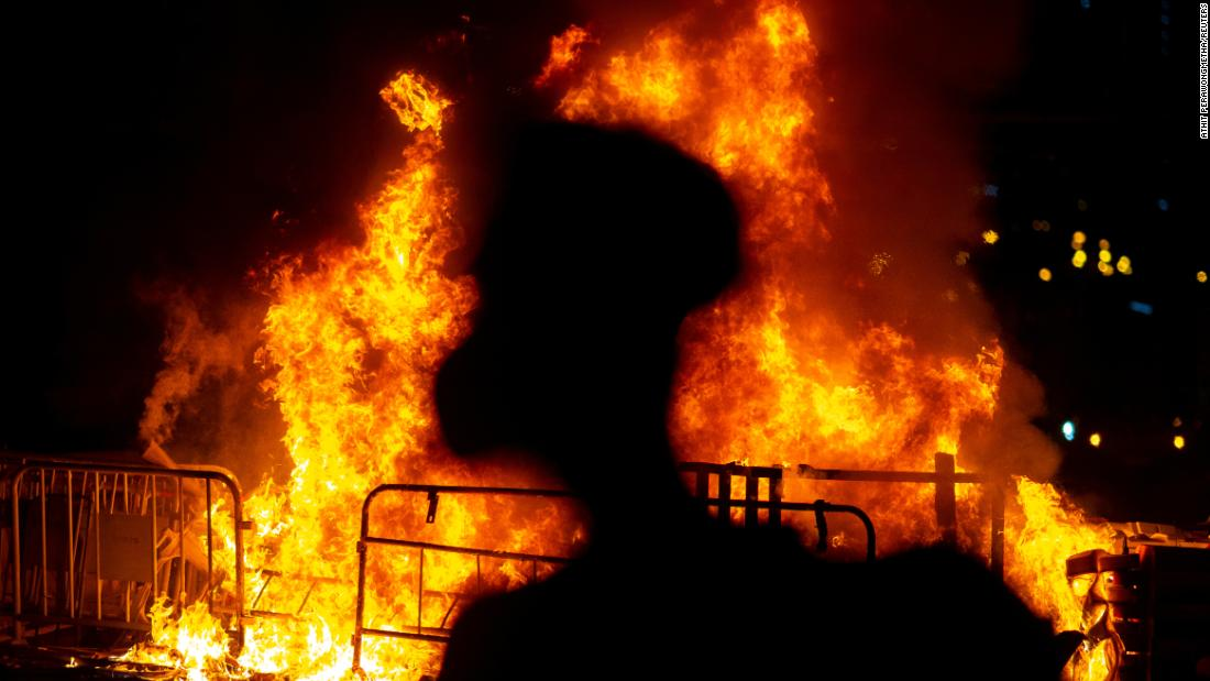 An anti-government protester stands near a fire on Friday, October 4.