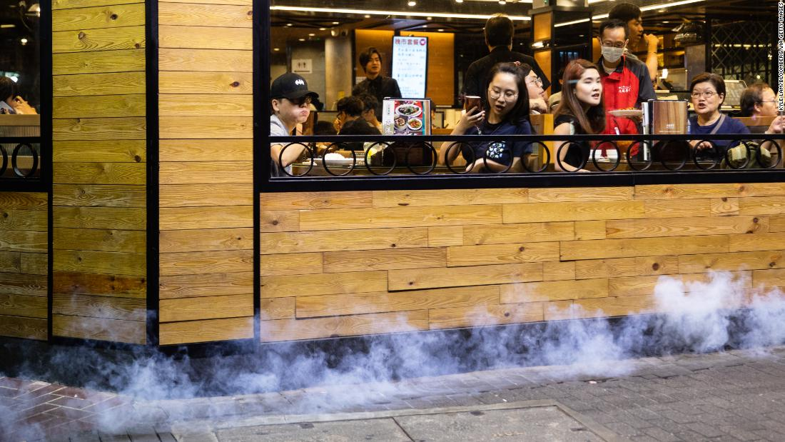 Police deploy tear gas outside a restaurant during a protest in the Causeway Bay district.