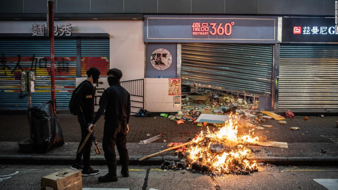 A fire is seen in front of a store vandalized by protesters.