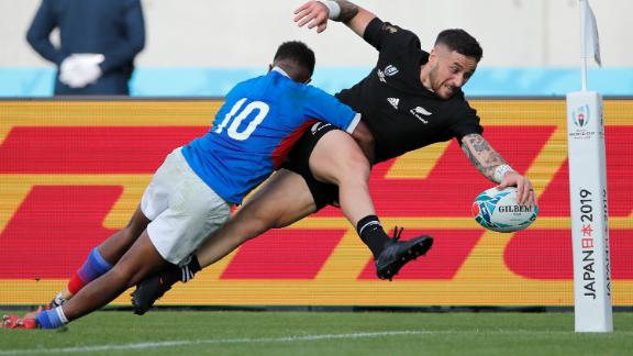 New Zealand's T J Perenara is about to score a try as he is tackled by Namibia's Helarius Kisting.