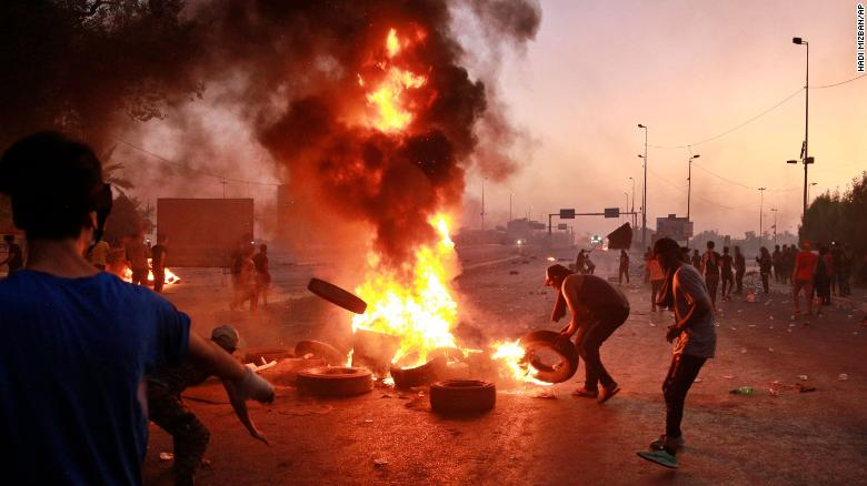 Iraqi security forces fire tear gas while anti-government protesters set fires in Baghdad on October 5.