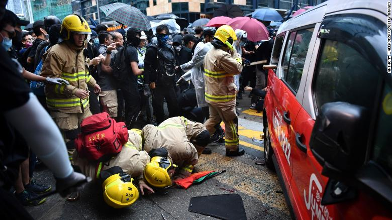 Rescue personnel check underneath a taxi after it hit two protesters along Cheung Sha Wan Road in Hong Kong on Sunday.