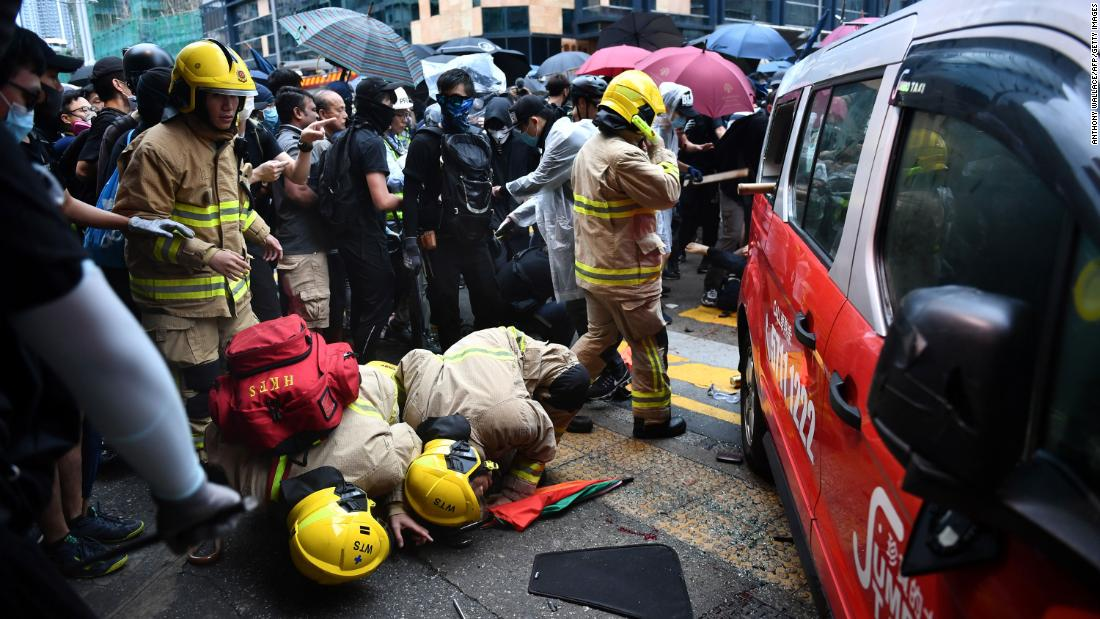 Rescue personnel check the bottom of a taxi after the driver allegedly drove onto the pavement, hitting protesters in Hong Kong on October 6.