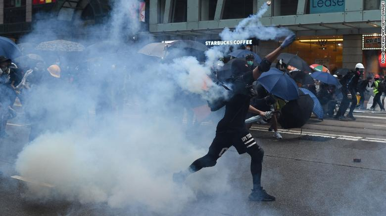 A protester throws back a teargas cannister towards police in the Wanchai district in Hong Kong on Sunday.