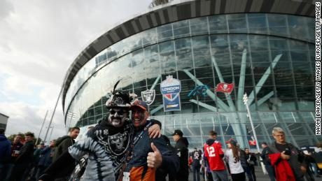 Fans pose outside the game between Chicago Bears and Oakland Raiders at Tottenham Hotspur Stadium in London.