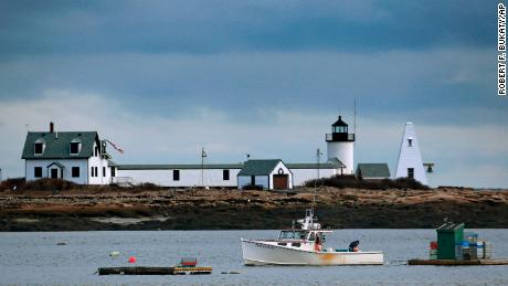 A lobster boat passes by the Goat Island Light at Cape Porpoise in Kennebunkport, Maine.