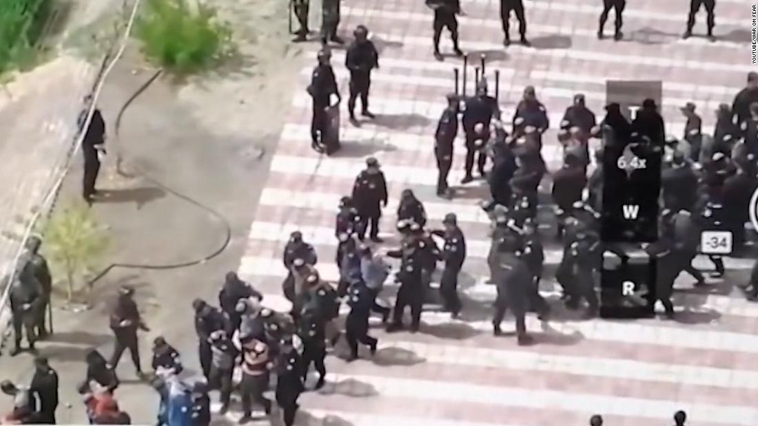 Melihat drone video yang menunjukkan ratusan terikat laki-laki