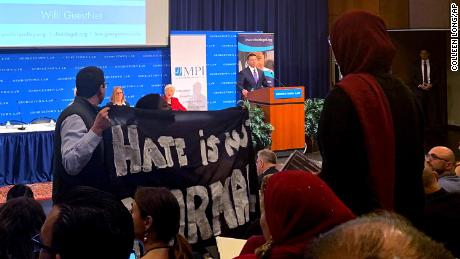 "Acting Homeland Security Secretary Kevin McAleenan takes the podium at a immigration law and policy conference, Monday, October 7, in Washington. As he took the stage, a handful of protesters stood up and held large black banners, one read ""Hate is Not Normal,"" and shouted out that children were under attack."