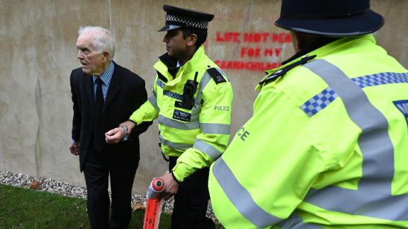 Police officers detain climate change activist Phil Kingston outside the UK Treasury.