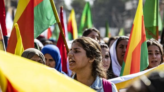 Syrian Kurdish women carry flags and banners as they demonstrate against Turkish threats to launch a military operation on their region in northeastern Syrian on October 7, 2019.