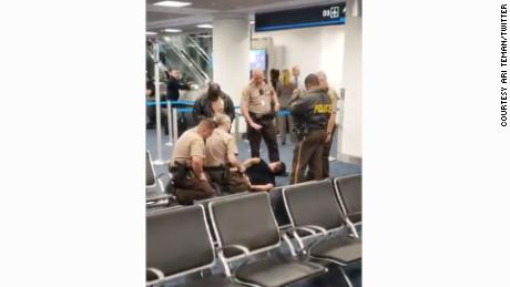 The passenger who forced his way onto an American Airlines flight was removed and taken to a hospital for evaluation.