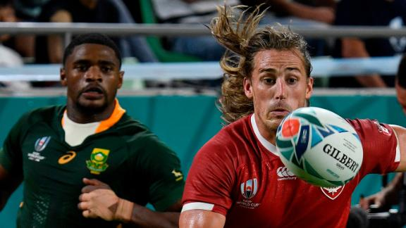 Canada's Jeff Hassler runs for the ball during the Pool B match against South Africa but his side were on the wrong end of a 66-7 drubbing.