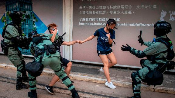 TOPSHOT - Police chase down a couple wearing facemasks in the central district in Hong Kong on October 5, 2019, a day after the city