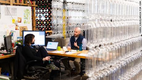 Szaky, left, speaks with a coworker in his office. Recycled plastic bottles form a curtain that walls off his office at the TerraCycle headquarters in Trenton, New Jersey. (Mark Kauzlarich for CNN)