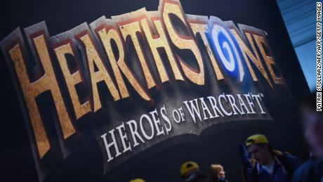 "Visitors of the ""Gamescom"" pass a display of the ""HEARTHSTONE"" game on August 14, 2014 during the Gamescom fair in Cologne, western Germany. The trade fair for interactive games is running until August 17, 2014. PHOTO / PATRIK STOLLARZ        (Photo credit should read PATRIK STOLLARZ/AFP/Getty Images)"