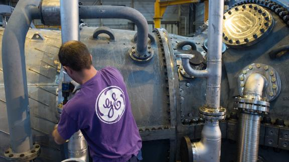 An employee of US multinational General Electric (GE) works on a gas turbine at the GE plant in Belfort, eastern France, on October 27, 2015. AFP PHOTO / SEBASTIEN BOZON        (Photo credit should read SEBASTIEN BOZON/AFP/Getty Images)