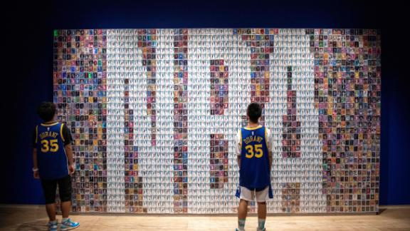 Two Chinese youths stand in front of a wall displaying basketball trading cards at the NBA exhibition in Beijing on August 19, 2019.