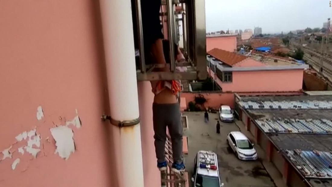 Chinesischer junge, baumelt vier Stockwerke über dem Boden nach der Kopf wird geklebt im Fenster Sicherheit bars