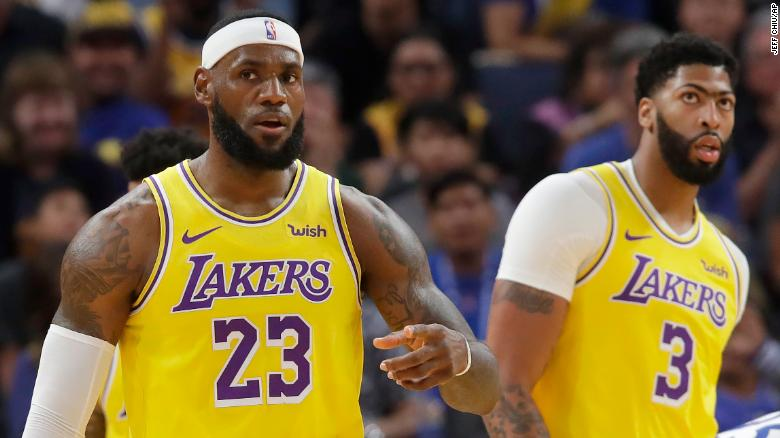 Los Angeles Lakers forward LeBron James (23) in front of forward Anthony Davis (3) during the first half of a preseason NBA basketball game against the Golden State Warriors in San Francisco.