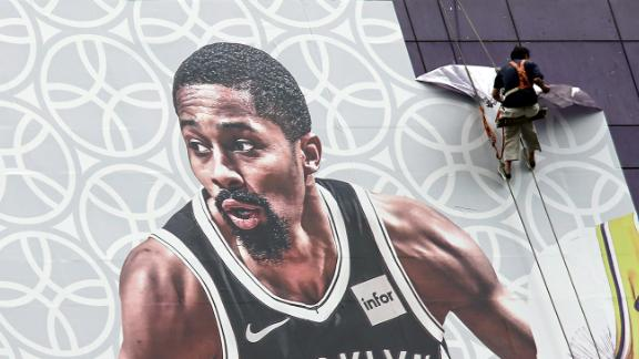 A worker takes down a billboard advertising an NBA preseason basketball game on Thursday between the Los Angeles Lakers and Brooklyn Nets in Shanghai, China, Wednesday, Oct. 9, 2019. The NBA has postponed Wednesday's scheduled media sessions in Shanghai for the Brooklyn Nets and Los Angeles Lakers, and it remains unclear if the teams will play in China this week as scheduled. (AP Photo)