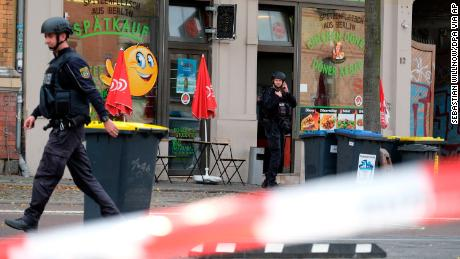 A police officer walks in front of a kebab grill in Halle, Germany, Wednesday, Oct. 9, 2019. A gunman fired several shots on Wednesday in the German city of Halle. Police say a person has been arrested after a shooting that left two people dead. (Sebastian Willnow/dpa via AP)