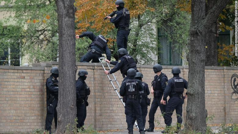 Policemen climb over a wall close to the site of a shooting in Halle, eastern Germany.