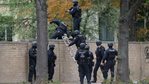 "Policemen climb over a wall close to the site of a shooting in Halle an der Saale, eastern Germany, on October 9, 2019. - At least two people were killed in a shooting on a street in the German city of Halle, police said, adding that the perpetrators were on the run. ""Early indications show that two people were killed in Halle. Several shots were fired. The suspected perpetrators fled in a car,"" said police on Twitter, urging residents in the area to stay indoors. (Photo by Sebastian Willnow / dpa / AFP) / Germany OUT (Photo by SEBASTIAN WILLNOW/dpa/AFP via Getty Images)"