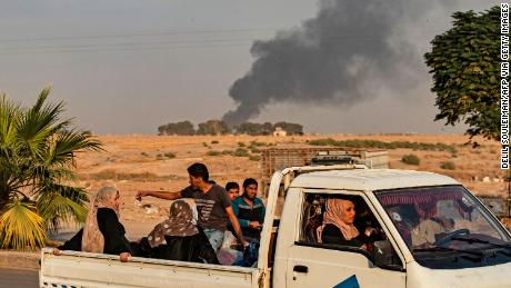 Civilians ride a pickup truck as smoke billows following Turkish bombardment on Syria's northeastern town of Ras al-Ain.