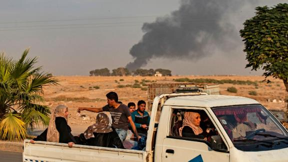 Civilians ride a pickup truck as smoke billows following Turkish bombardment on Syria's northeastern town of Ras al-Ain.