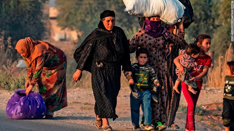 Civilians flee amid Turkish bombardment on Syria's northeastern town of Ras al-Ain in the Hasakeh province along the Turkish border on October 9, 2019.