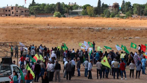 Kurdish people in Ras al-Ain, Syria, wave their group