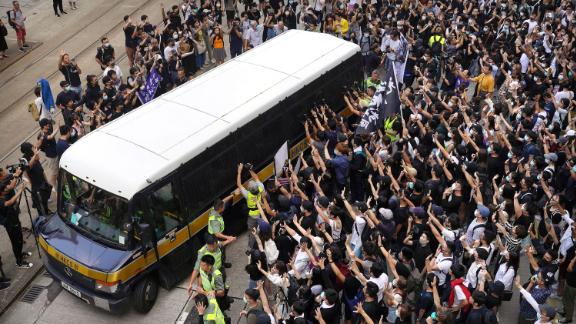Supporters surround a police bus carrying political activist Edward Leung as it leaves the High Court in Hong Kong on Wednesday, October 9. Several hundred masked protesters gathered at Hong Kong