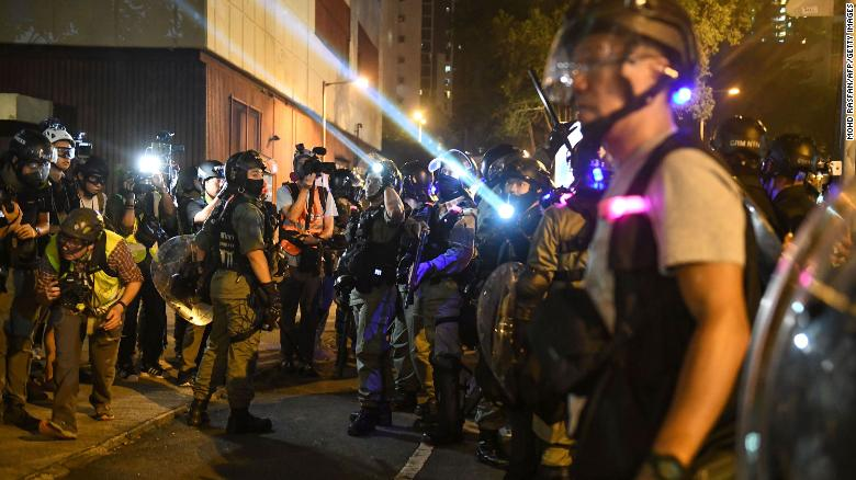Riot police shine lights at protesters outside Ma On Shan police station in the New Territories of Hong Kong on October 9.