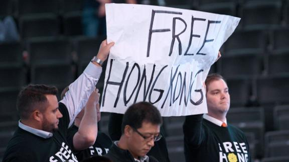 Activists hold up a sign before an NBA exhibition basketball game between the Washington Wizards and the Guangzhou Loong-Lions, Wednesday in Washington.