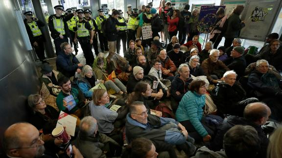 Police Officers stand guard as Extinction Rebellion demonstrators peacefully block an entrance to City Airport in London, Thursday, Oct. 10, 2019. Some hundreds of climate change activists are in London during a fourth day of world protests by the Extinction Rebellion movement to demand more urgent actions to counter global warming. (AP Photo/Matt Dunham)