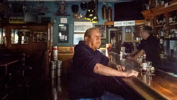 Joseph Pokorski drinks a beer at the Town Square as downtown Sonoma, California, remains without power on Wednesday.