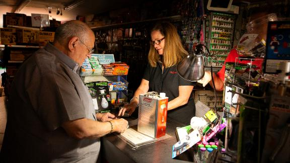Tom Hyde, left, buys a can of fuel for his Coleman camp stove from Kim Scheffer at a Village True Value Hardware store in Santa Rosa, Calif., Wednesday, Oct. 9, 2019. Pacific Gas & Electric has cut power to more than half a million customers in Northern California hoping to prevent wildfires during dry, windy weather throughout the region. (John Burgess/The Press Democrat via AP)