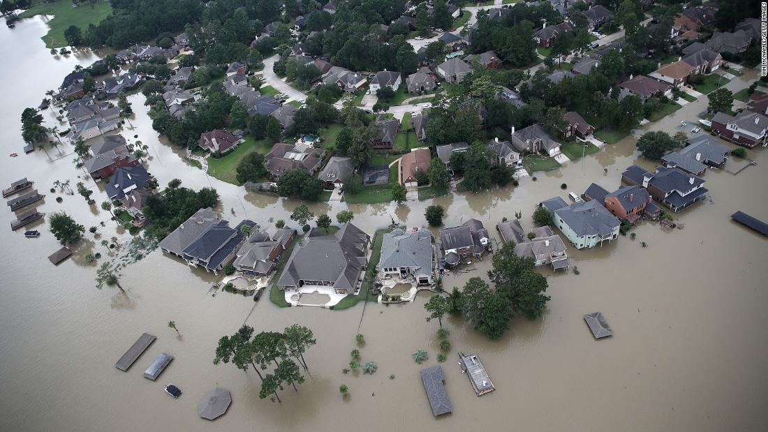 Flooded homes are shown near Lake Houston following Hurricane Harvey on August 30, 2017, in Houston. A new report finds that current flood insurance coverage rates greatly underestimate the actual financial risk flooding poses to millions of homeowners.