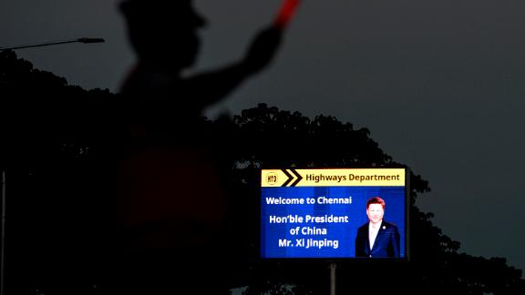 A traffic policeman stands beside a welcoming board for China's President Xi Jinping in Chennai on October 9, 2019, ahead of a summit with his Indian counterpart Narendra Modi held at the World Heritage Site of Mahabalipuram from October 11 to 13 in Tamil Nadu state.