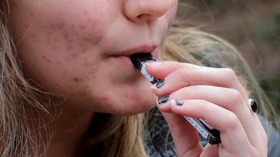 FILE - In this April 11, 2018, file photo, a high school student uses a vaping device near a school campus in Cambridge, Mass. Schools have been wrestling with how to balance discipline with treatment in their response to the soaring numbers of vaping students. Using e-cigarettes, often called vaping, has now overtaken smoking traditional cigarettes in popularity among students, says the Centers for Disease Control and Prevention. Last year, one in five U.S. high school students reported vaping the previous month, according to a CDC survey. (AP Photo/Steven Senne, File)
