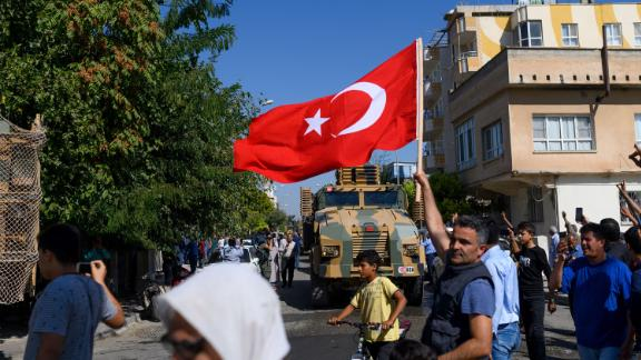 TOPSHOT - A man waves a Turkish flag as Turkey-backed Syrian opposition fighters going to Tel Abyad from Turkish gate towards Syria in Akcakale in Sanliurfa province on October 10, 2019. - Turkey has launched a broad assault on Kurdish-controlled areas in northeastern Syria, with intensive bombardment followed by a ground offensive made possible by the withdrawal of US troops. (Photo by BULENT KILIC / AFP) (Photo by BULENT KILIC/AFP via Getty Images)