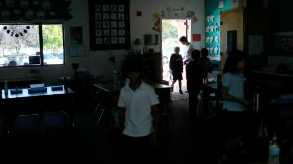 Students walk back into  class after a recess at a school in San Jose, California. They relied on sunlight after a Pacific Gas & Electric power shutdown turned out the lights.