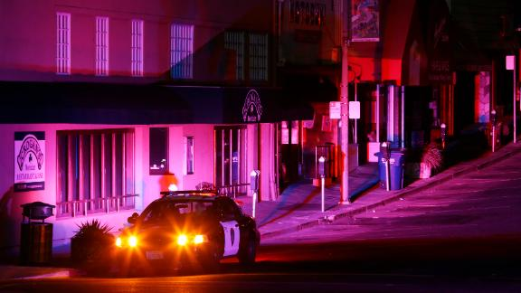 Police officers patrol a street during a power outage in Oakland, California.