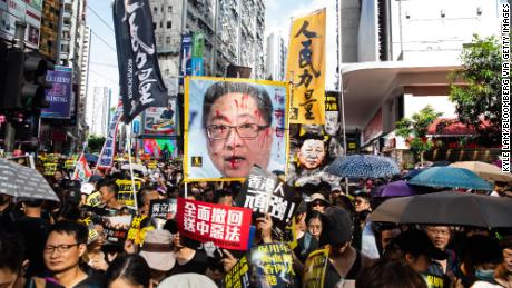Protesters hold banners and placards including a defaced poster of Hong Kong Police Commissioner Stephen Lo as they march during the annual pro-democracy rally on July 1.