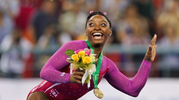 Biles dodges a bee flying near her during the medal ceremony after winning gold in the women's all-around final of the 2014 World Championships.