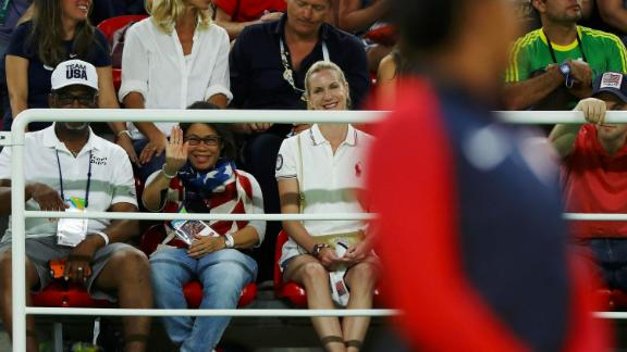 Biles' grandfather, Ron Biles, and his wife, Nellie, watch as she waits on the podium to receive her gold medal after winning the women's floor final of the 2016 Olympics. They took in Simone and her younger sister, Adria, and then formally adopted them when Simone was just 6 because Simone's mom was battling addiction to drugs and alcohol.