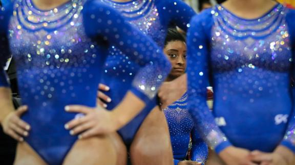 Biles rests behind teammates during qualifying sessions for the 2018 World Chamionships in Doha, Qatar.