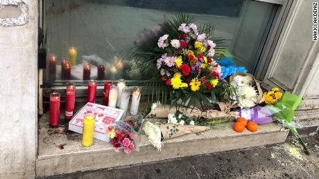 Flowers, candles and a pizza box adorn a makeshift memorial to the four homeless men killed in New York.