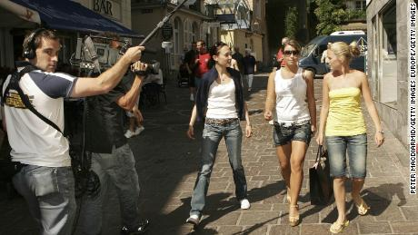 Years before starting the celebrity scandal of the century, Coleen McLoughlin (now Coleen Rooney, second right), is filmed by TV crews during the 2006 World Cup in Germany.